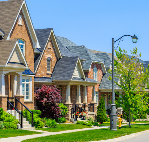 A picture of a neighborhood street showing the front of homes, sidewalk , grass, street light and trees.