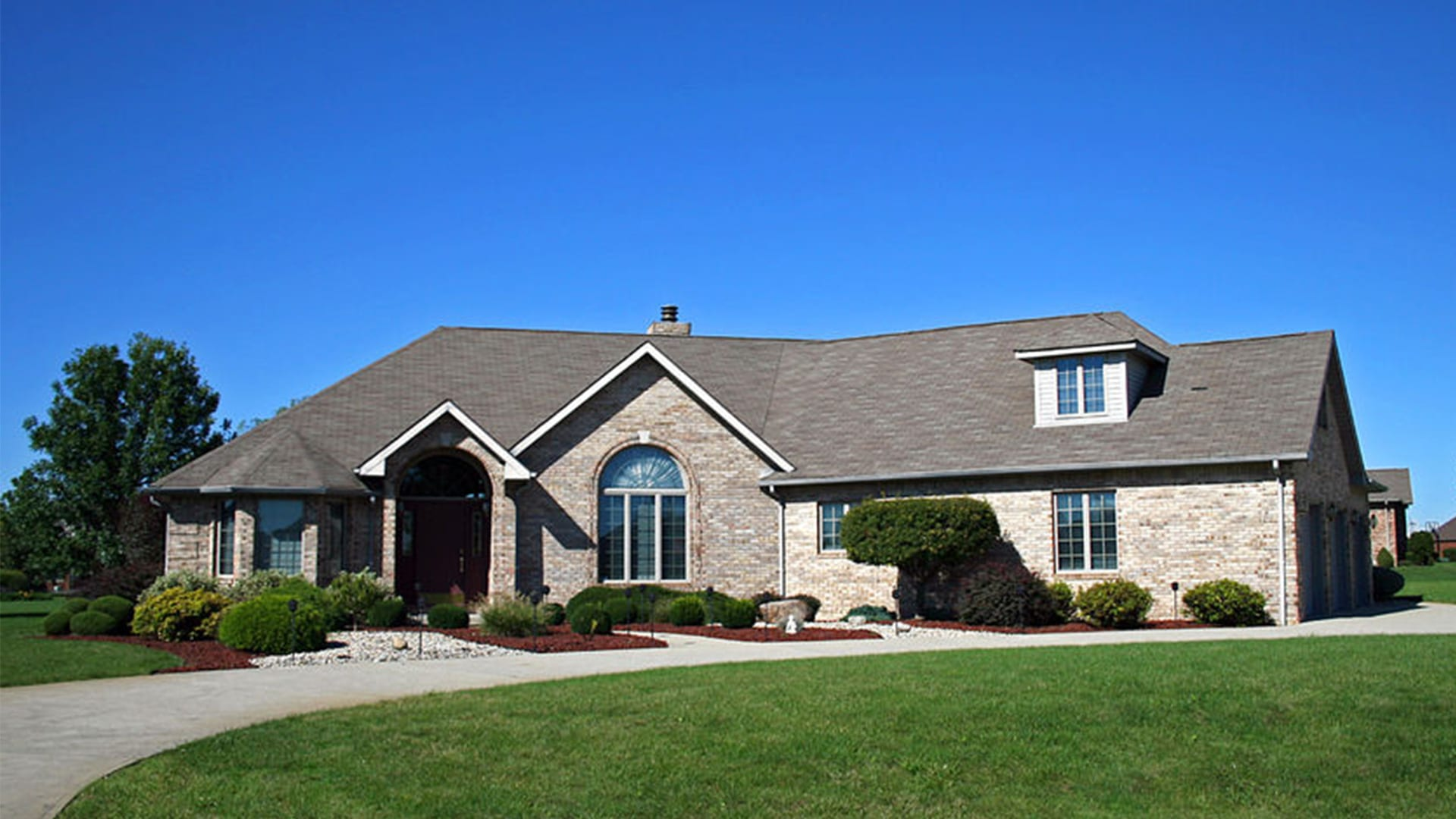 Photograph of a light brick home with beautiful landscaping.