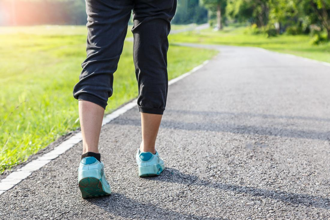 person-walking-with-a-steady-gait-around-running-track-outdoors-in-sports-clothes
