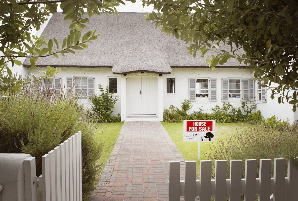 Small white home with a white picket fence, and a house for sale sign.