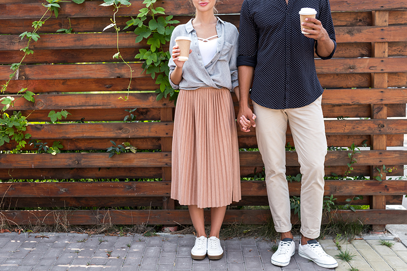 Photo of a couple holding hands each with a cup of coffee in the other hand.