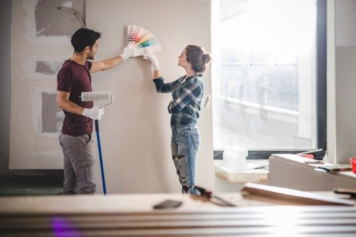 Man and woman holing color swatches against a wall to decide what color to paint it.
